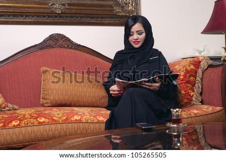 elegant arabian lady with hijab relaxing in salon reading magazine - stock photo