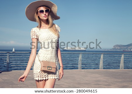 Elegant attractive young woman posing in sunglasses and hat on vacation day. Sea on background. Blue sky. - stock photo