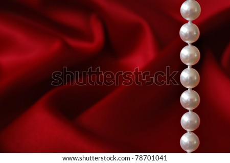 Elegant background image of beautiful cultured pearls against a red satin background.  Macro with shallow dof and copy space.  Selective focus limited to the pearls. - stock photo
