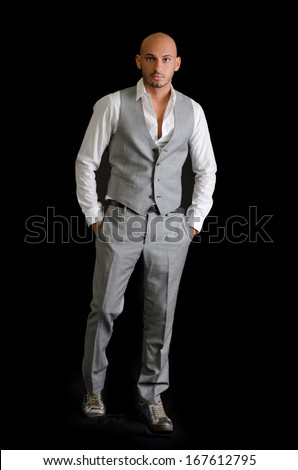 Elegant, bald young man in business suit on dark background, looking at camera - stock photo