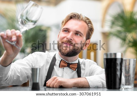 Elegant barman checking the cleanliness of glass at the restaurant - stock photo