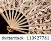 Elegant battenberg lace fan on dark background.  Highly detailed macro in sepia tones. - stock photo