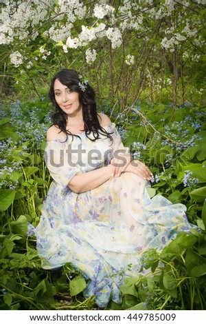 Elegant beautiful adult woman posing in the spring garden