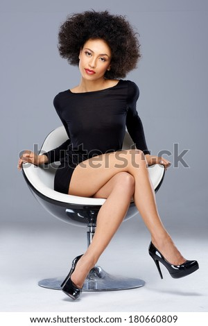 Elegant beautiful African American woman in a black cocktail dress and high heels sitting in a contemporary armchair on a grey background