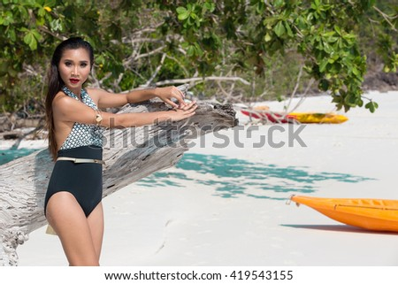 Elegant Beautiful Asian Thai Woman Girl with perfect body Fashion Swim Suit at sand Ocean Beach, old age Timber tree and Kayak Canoe