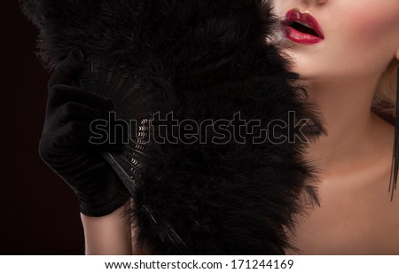 elegant Beautiful blonde lady with black feather fan. studio portrait - stock photo