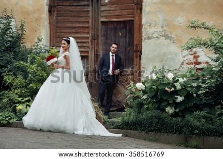 Elegant beautiful brunette bride walking down old european street with handsome groom in the background