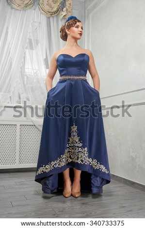 Elegant, beautiful, fashionable woman, girl, brunette in a long blue dress with embroidery, hands in the pockets of clothes; in the room; beige shoes. - stock photo