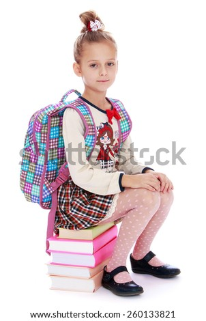 elegant beautiful schoolgirl sitting on a stack of books - isolated on white. - stock photo