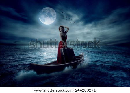 Elegant beautiful stylish woman with suitcase standing on a boat in a middle of the ocean after storm drifting away from her past on moonlight sky clouds background. Conceptual landscape screen saver  - stock photo