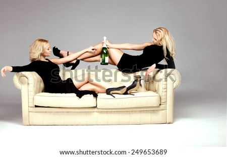 Elegant beautiful two woman relaxing, drinking champagne. Blonde girls with long slim legs. - stock photo