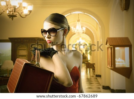 Elegant beautiful woman holding a bag in a luxury room - stock photo