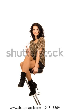 Elegant beautiful woman sitting on a contemporary metal bar stool enjoying a flute of champagne while out partying, isolated on white - stock photo