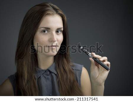 Elegant beautiful woman smoking e-cigarette - stock photo