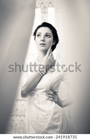 elegant beautiful young lady in white dress hiding in tulle curtain on copy space background, black & white portrait - stock photo
