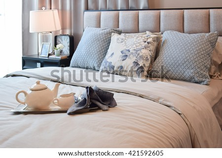 elegant bedroom interior design with floral pattern pillow and and decorative tea set on bed - stock photo