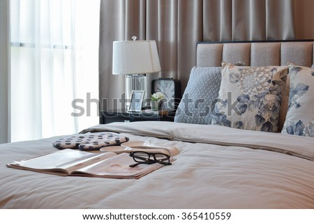 elegant bedroom interior design with floral pattern pillows on bed and decorative table lamp. - stock photo