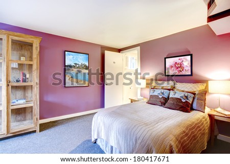 Elegant bedroom with beige carpet floor and contrast color bright red walls. Green and purple bedding blend perfectly with red wall - stock photo