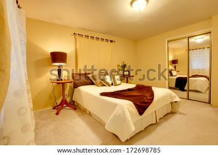 Elegant bedroom with light yellow walls and matched bedroom cloth set, walk-in closet - stock photo