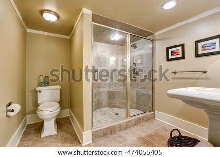 elegant beige bathroom interior with modern glass walk in shower toilet and washbasin stand