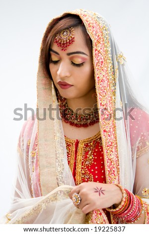 Elegant Bengali bride arranging veil looking down, isolated - stock photo