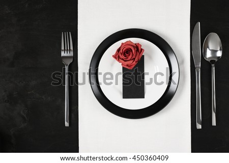 Elegant black and white table setting: plates on linen, blank label with red rose and silverware. Top view point.