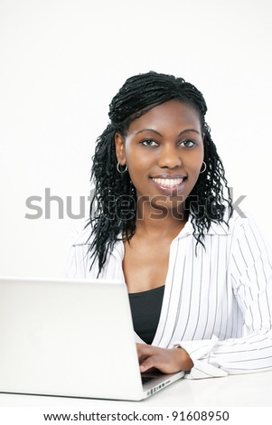 Elegant black female executive or bank manager sitting at office desk with computer