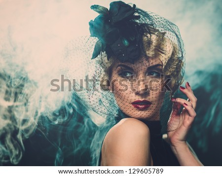 Elegant blond retro woman  wearing little hat with veil in smoke - stock photo