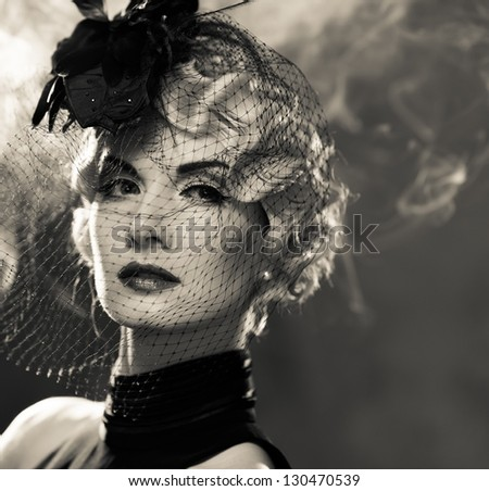 Elegant blond retro woman  with red lipstick wearing little hat with veil in smoke - stock photo