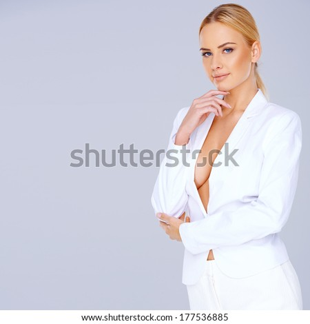 Elegant blond woman wearing a white suit with a plunging neckline giving a view of her breast standing sideways looking thoughtfully at the camera with copyspace - stock photo