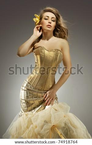 Elegant blonde beauty posing in a golden dress - stock photo