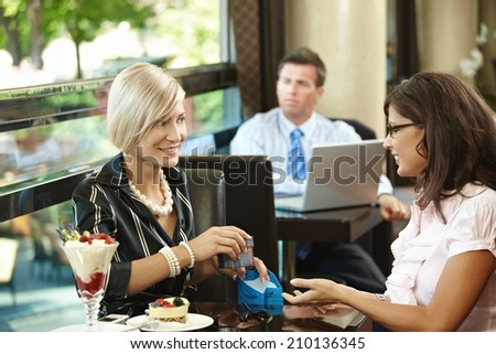 Elegant blonde caucasian businesswoman giving gift at restaurant. Sitting at table, smiling, gift box in hand, ice cream on table, indoor. - stock photo