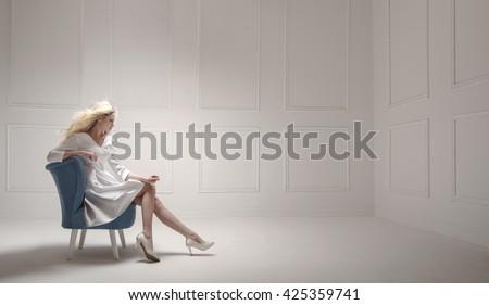 Elegant blonde in an empty room - stock photo