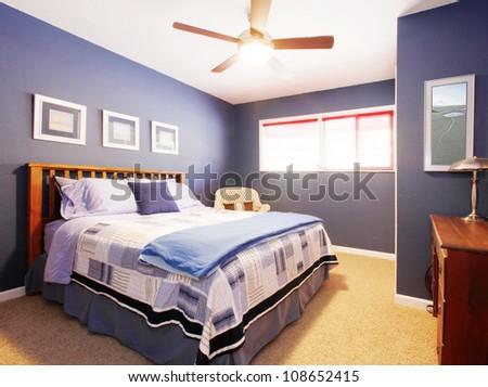 Elegant blue bedroom with yellow carpet. - stock photo