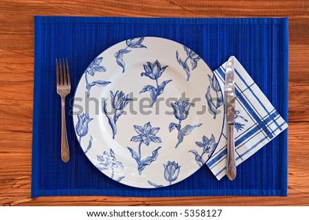 Elegant Blue Porcelain eating set with silverware on wooden background - stock photo
