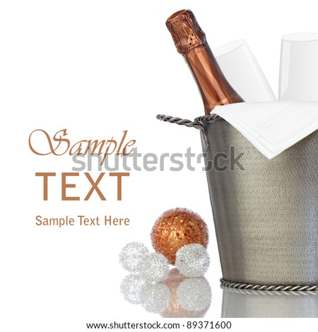 Elegant Bottle Of Champagne with Linen Napkin and Crystal Glass Flutes Chilling in Vintage Textured Hammered Metal Wine Bucket With Bronze & Silver Holiday Decorations ~ Isolated On White Background - stock photo