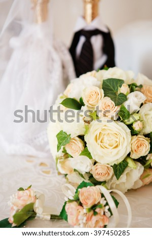 Elegant bridal bouquet and groom's boutonniere of roses and and decorated champagne bottle - stock photo