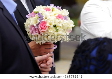 elegant bridal bouquet in groom's hand - stock photo