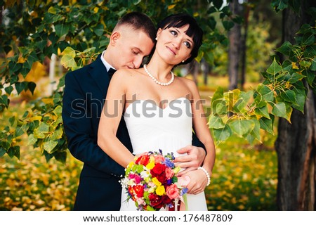 Elegant bride and groom posing together outdoors in a park on a wedding day. Elegant bride and groom posing together outdoors on a wedding day. wedding dress. Bridal wedding bouquet of flowers