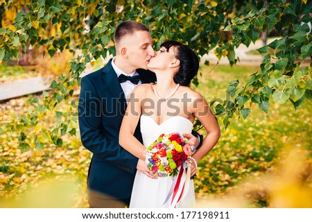 Elegant bride and groom posing together outdoors in a park on a wedding day. Elegant bride and groom posing together outdoors on a wedding day. wedding dress. Bridal wedding bouquet of flowers - stock photo