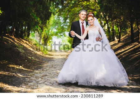 Elegant bride and groom posing together outdoors on a wedding day. Groom and Bride in a park. wedding dress. Bridal wedding bouquet of flowers - stock photo