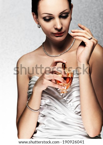 elegant bride applying perfume on her wrist - stock photo