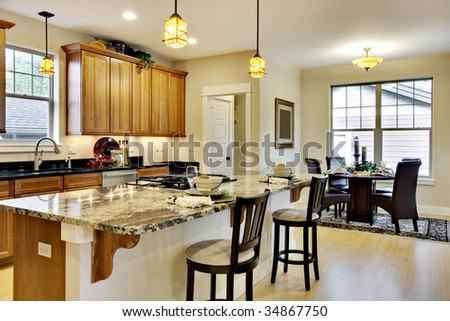 Elegant, brightly lit kitchen with island and light wood cabinetry - stock photo