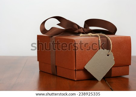 Elegant brown present with brown ribbon and rustic gift tag - stock photo