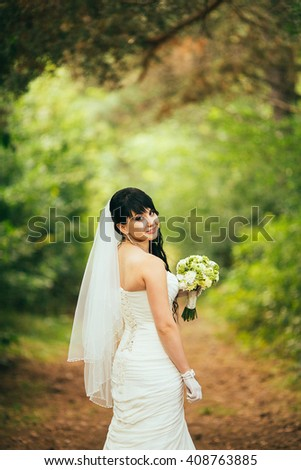 Elegant brunette bride posing outdoors with a bouquet on her wedding day