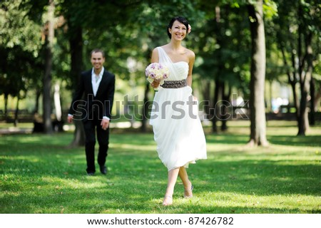 Elegant brunette bride posing outdoors with a bouquet on her wedding day - stock photo
