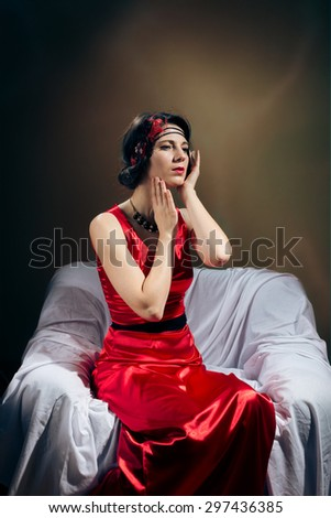 Elegant brunette girl in red gown talking on cellphone.