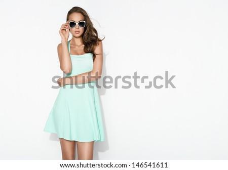 elegant brunette in mint dress and sunglasses posing in the studio  - stock photo
