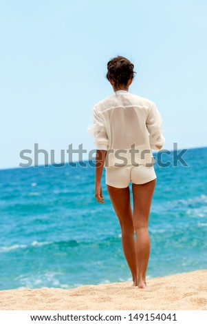 Elegant brunette in white outfit walking towards blue sea. - stock photo