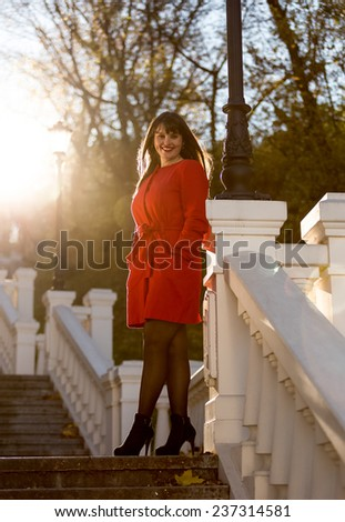 Elegant brunette woman in red coat standing on stone stairs at sunny day - stock photo